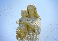 Close-up Of Statue Of Mary And Jesus Against Blue Background