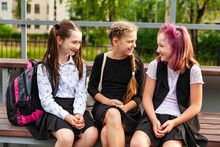 Teenage Girls In School Clothes Have Fun Sitting On The Podium Of The School Stadium.