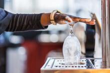 Crop Bartender Using Glass Rinser In Bar