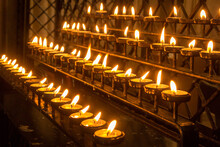 Illuminated Candles Burning In Temple