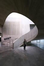Man Standing In Hallway Of Modern Art Museum