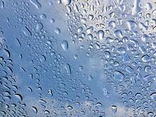 Full Frame Shot Of Raindrops On Glass Window Against Sky
