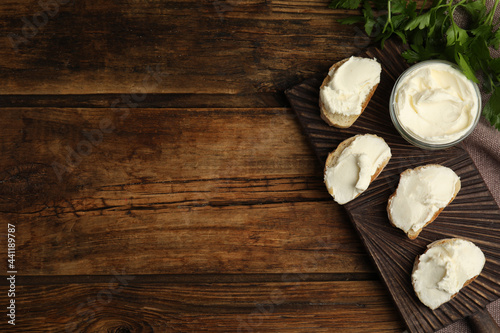Fotografering Bread with cream cheese on wooden table, flat lay. Space for text