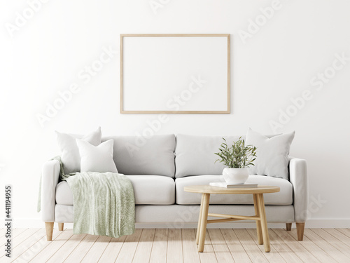Fototapeta Horizontal poster mockup with wooden frame in living room interior with grey sofa, pillows, green throw, olive twigs in vase and coffee table on empty wall background