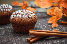 Chocolate Muffins With Apple Filling On A Background Of Autumn Leaves And Cinnamon