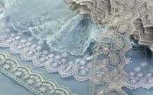 Pile Of Blue, White, Gray Gentle Guipure, Lace Fabric On Blue Background. Use For Atelier