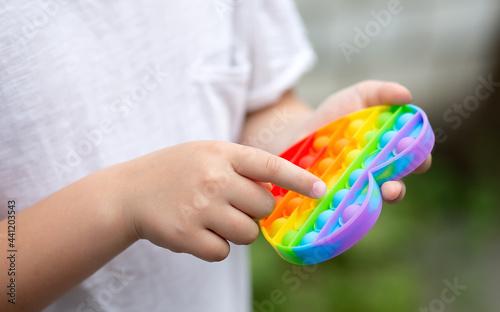 Obraz na plátně Colorful antistress sensory toy fidget push pop it in kid's hands