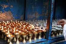 Midsection Of Person Holding Candles Burning In Temple