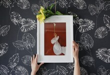 Hands Hanging A Framed Picture On A Wall