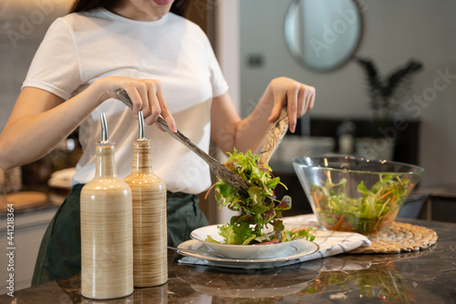 Murais de parede Happy young asian woman standing in kitchenand cooking healthy food