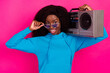 Leinwandbild Motiv Photo of cheerful nice afro american young woman hold shoulder boombox wear sunglass isolated on pink color background