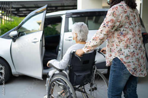 Fotografia Help and support asian senior or elderly old lady woman patient sitting on wheelchair prepare get to her car, healthy strong medical concept