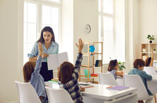 Little Kids Are Always Eager To Learn Something New: Elementary Students Raise Hands Willing To Answer Teacher's Question In Class. Concept Of Keeping Elementary School Education Fun And Interesting