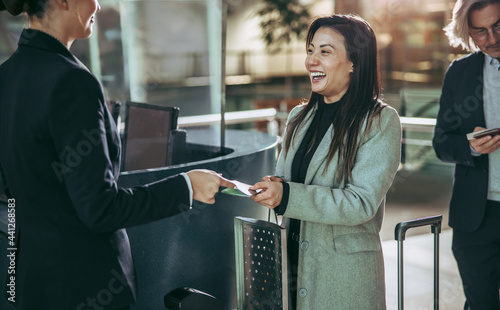 Businesswoman doing flight check in at airport