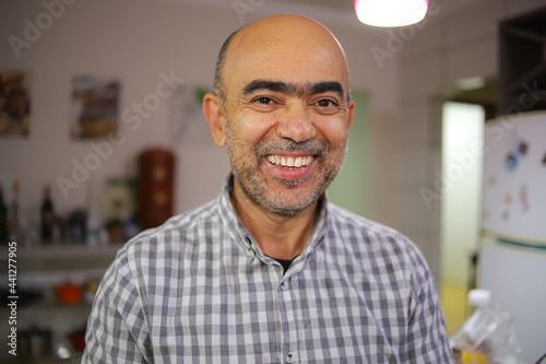 Carta da parati Homem de acima de 50 anos, sorrindo, de camisa xadrez, dentro de uma cozinha