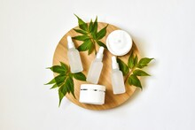 White Bottles With Pipettes, Moisturizer Cream Jars On A Round Wooden Cut With Green Leaves On A White Background. Set Of Eco Natural Cosmetics. Copy Space. Bioorganic Cosmetic Product.