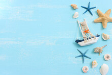 Nautical Concept With White Decorative Sail Boat, Seashells Over Blue Wooden Background