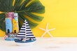 Leinwandbild Motiv Nautical concept with sea life style objects as boat, driftwood beach houses, seashells and starfish over wooden table and yellow background
