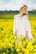 Leinwandbild Motiv Young woman in yellow oilseed rape field posing in white dress outdoor