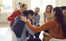 People Group Therapy And Support. Participant Giving Support To Crying Sad Man During Therapeutic Group Meeting Or Phycology Training Session. Side View At Upset Guy Feel Pain Depression Problem
