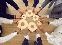 Professional Business Team Connecting Cogwheels As Metaphor For Good Teamwork, Synergy, Effective Cooperation And Management. High Angle, From Above, Top View Closeup Shot Of Human Hands Holding Cogs