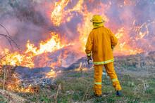 A Fireman Stands Watch Over A Blazing Grass Fire