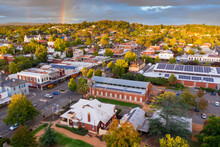 Aerial View Of Rainbow And Cloud Formations Over A Regional Town's Historic Streetscape