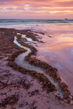 A Colorful Coastal Sunset Reflected In The Water Of An S Shaped Rock Pool