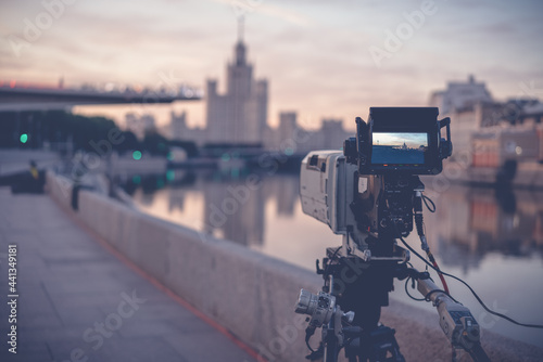 Fotografie, Obraz A professional video camera stands on a tripod recording the city and the river
