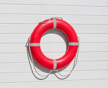 Red Lifebuoy Ring Hanging On White Wooden Wall