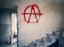 The Ruins Of An Old Abandoned House, With An Anarchist Sign Painted In Red On A Wall. Silent, Spooky Location.