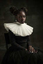 Portrait Of Medieval African Young Woman In Black Vintage Dress With Big White Collar Posing Isolated On Dark Green Background.