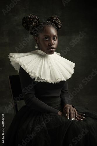 Billede på lærred Portrait of medieval African young woman in black vintage dress with big white collar posing isolated on dark green background