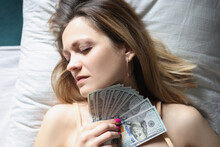 Young Woman Sleeping In Bed With Dollar Bills In Her Hands