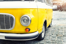 Close-up Detail Front View Of Headlight Part Old Vintage Bright Yellow Retro Mini Bus Car Van Parked In European City Center On Cobble Stone Paved Road. Fun Vehicle For Snack Delivery Sale Journey