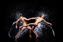 Couple Of Athletic Women Are Doing Dancing Tricks Under Streams, Splashes, Drops Of Rain Water. Duo Acrobats, Ballet Dancers Are Performing Dance. Freedom And Freshness Concept. Modern Art And Beauty.