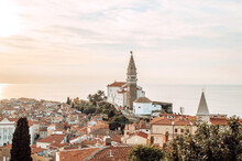 A Panoramic Of Old Town Piran, Slovenia At Sunset. View Over The Tiled Roofs Of Piran And The Adriatic Sea.