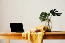 Laptop And Books On Table With Vase