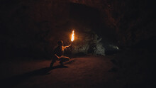 Explorer With Burning Torch In Cave
