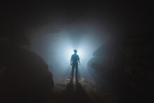 Unrecognizable Man Standing In Narrow Cave