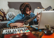 Musician Playing On Guitar Near Laptop At Home