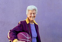 Senior Sportswoman With Basketball On Purple Background