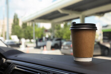 Paper Coffee Cup On Car Dashboard At Gas Station. Space For Text