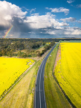 Aerial View Of A Country Road Running Through Farmland With Clouds And A Rainbow In The Distance