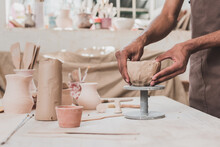 Partial View Of Young African American Man Sculpting Clay Pot With Hands On Table With Equipment In Pottery