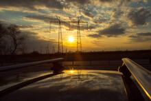 Power Lines On The Background Of Beautiful Nature. Electric Poles With Wires Are Reflected On The Roof Of The Car.