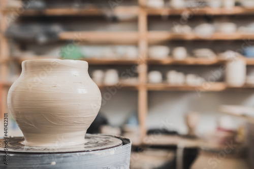 Photo wet clay pot on pottery wheel on wooden bench in art studio