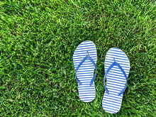 Pair Of Blue Striped Sandals On Green Grass, Casual Classic Footwear Style In Summer. Top View Informal Shoes, Pattern Design On Flip Flops, Comfortable Slippers At The Outdoor Park. Leisure Concept.