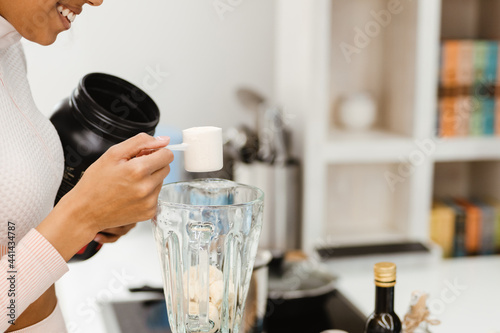 Obraz na plátne Black woman in headphones making smoothie with protein at home
