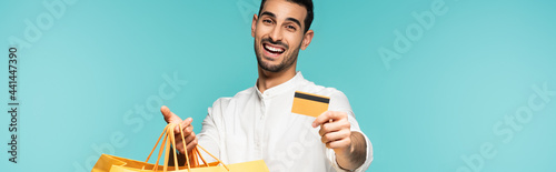 Fotografija Happy man with credit card and shopping bags isolated on blue, banner
